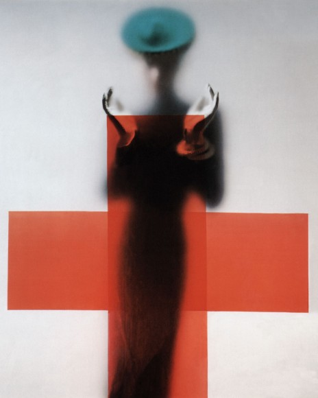 Woman silhouetted under red cross